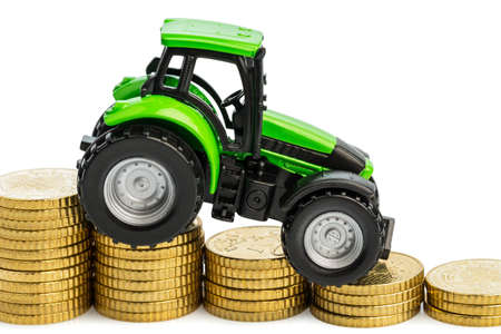 peasantry: farmers in agriculture have to reckon with rising costs  higher preies in food, fertilizer and plants  tractor with coins Stock Photo