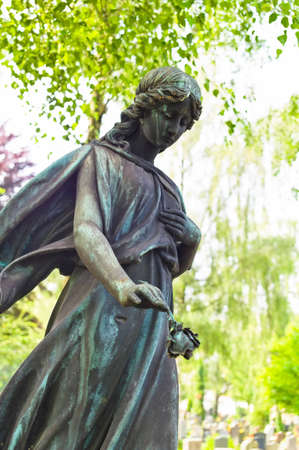 an angel watches as a statue on the tomb in a cemetery photo