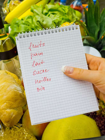 local supply: a woman holding a shopping list in a supermarket in the hand  french language