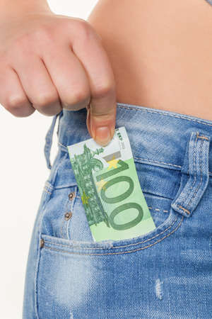 the hand of a young woman pulling a euro note from the pocket of her jeans Stock Photo - 17634576