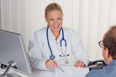 familiy: a young female doctor with stethoscope in her doctor s office  in an interview with a patient Stock Photo