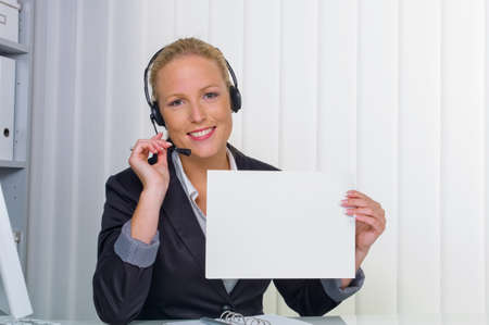 a friendly young woman with headset in customer service on the phone with a customer  friendly sales associate  photo