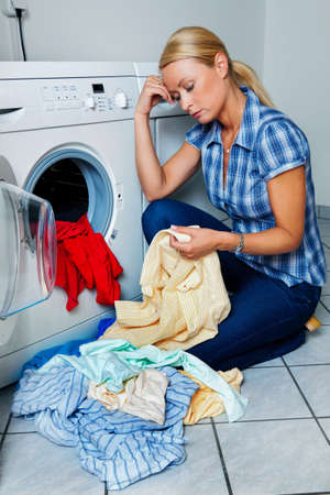 listless: a young housewife with washing machine and clothes  laundry day