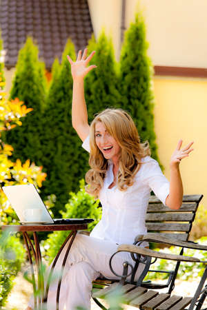 wlan: successful, laughing woman with laptop in garden