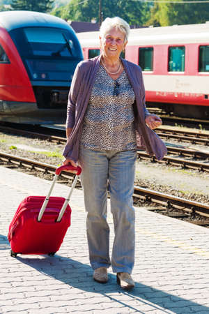 mature vital elderly couple at the train station  traveling on vacation photo