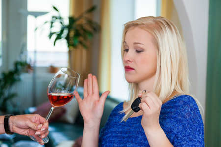 sobriety: a young woman with car keys refused a glass of wine  do not drink and drive