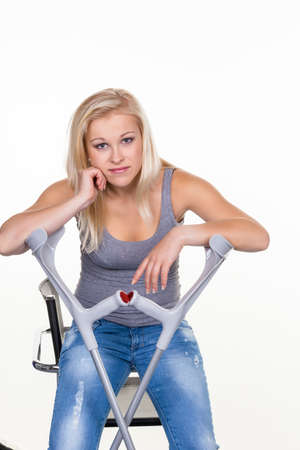 a young woman with crutches  symbolic photo for accidents, domestic accidents and insurance  photo