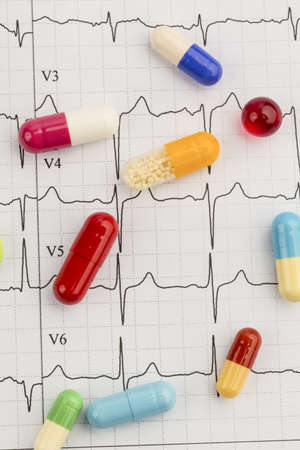 several tablets are on an ekg  symbolic for diseases of the cardiovascular system photo