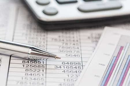 auditor�a: una calculadora est� en el buen n�meros del balance son las estad�sticas foto icono de las ventas, los beneficios y costos Foto de archivo