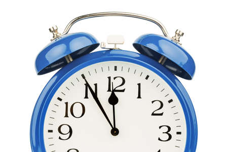five to twelve: a blue alarm clock on a white background  five to twelve Stock Photo