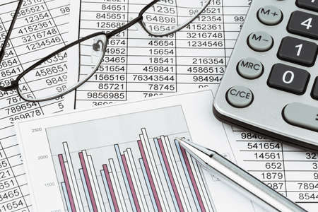 bookkeeping: a calculator is on a balance sheet numbers are statistics  photo icon for sales, profit and cost