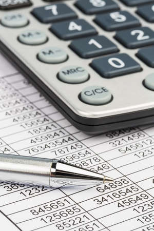 financial report: a calculator is on a balance sheet numbers are statistics  photo icon for sales, profit and cost