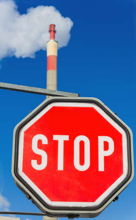 chimney of an industrial enterprise and stop sign  symbolic photo for environmental protection and ozone  photo