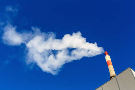 smoke stack: chimney of an industrial company with a strong smoke  symbolic photo for environmental protection and ozone