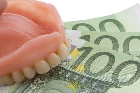 private insurance: denture and euro notes, symbolic photo for dentures, treatment costs and payment