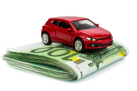toll: a car stands on euro banknotes  cost of purchasing a car, petrol, insurance and other car costs