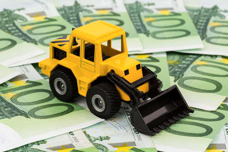 profitability: an excavator stands on euro banknotes  symbol photo for costs, revenues and grants in the construction industry and the construction industry