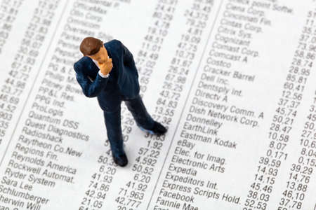 a small figure and the prices of shares in the newspaper  earn money on the stock market  gains and losses in stock trading  photo