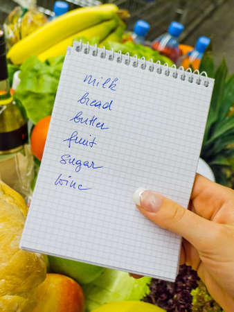 local supply: a woman holding a shopping list in a supermarket in the hand  english language