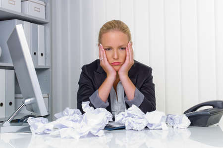 powerless: a woman in the office with paper balls  anger, stress and frustration in the workplace
