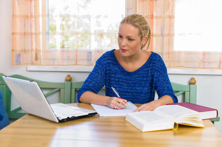 further education: a young student in studying for her degree in her apartment  Stock Photo