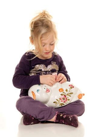 greenbacks: child with piggy bank with savings of greenbacks Stock Photo