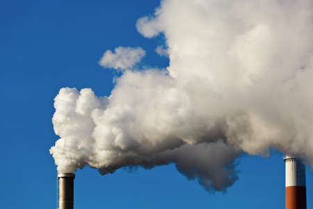 fuming: the smoking chimneys of a factory against a blue sky  smoke rises from chimneys white