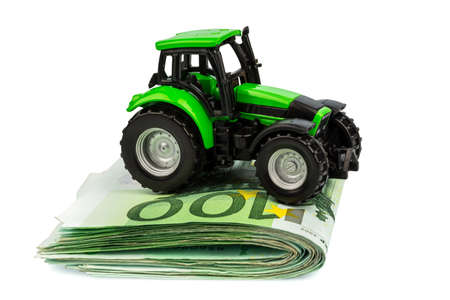 subsidy: a tractor stands on euro banknotes  symbol photo for costs, revenues and funding of a farmer in agriculture
