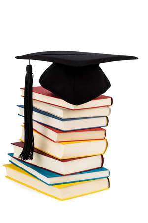 uni: a mortarboard on a pile of books, symbolic photo for education and skills Stock Photo