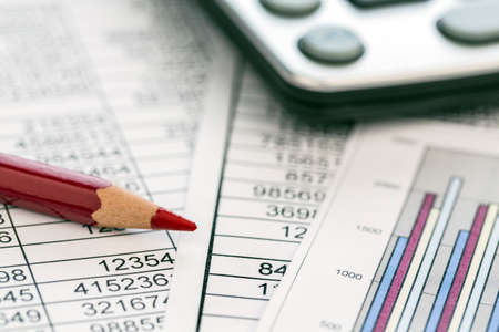 examiner: a calculator is on a balance sheet numbers are statistics  photo icon for sales, profit and cost