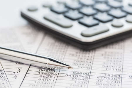 audit: a calculator is on a balance sheet numbers are statistics  photo icon for sales, profit and cost