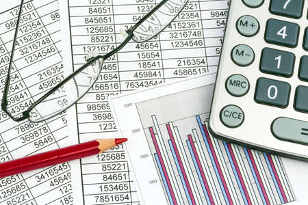 controlling: a calculator is on a balance sheet numbers are statistics  photo icon for sales, profit and cost