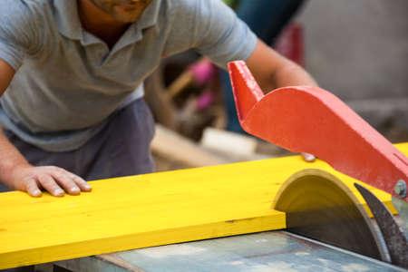 illicit: un operaio edile tagli legno per casseforme in un cantiere