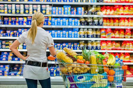 eine Frau mit dem breiten Spektrum im Supermarkt �berw�ltigt beim Einkauf Lizenzfreie Bilder