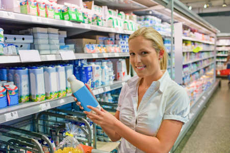 refrigerated: a young woman buys milk at the supermarket  stands in front of the refrigerated section  Stock Photo