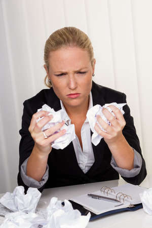 unsuspecting: a woman in the office with paper balls  anger, stress and frustration in the workplace