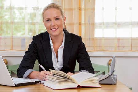 succesvolle jonge zakenvrouw op bureau met laptop en fractuur Stockfoto
