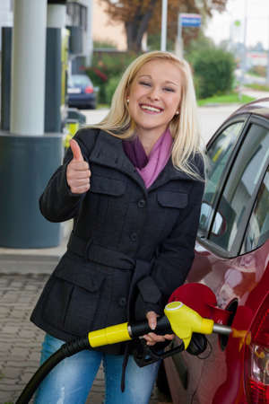 refuel: a young woman at a gas station gasoline tank  the cost of the car because of the gas prices are getting more expensive