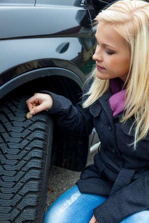 rodamiento: una mujer joven está midiendo la profundidad del dibujo de la llanta coche la profundidad adecuada en la banda de rodadura de un neumático puede evitar los accidentes Foto de archivo