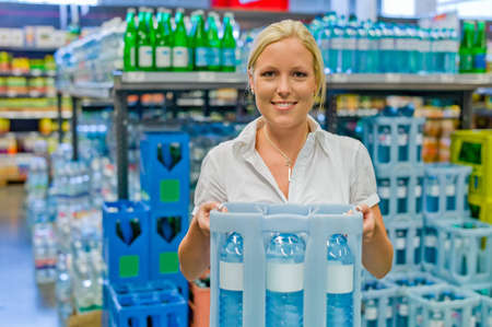 food supply: a young woman buys bottled water in the beverage department at the grocery store