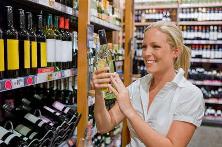 eine Frau kauft Wein in einem Supermarkt Weinregal mit Weinen aus der ganzen Welt