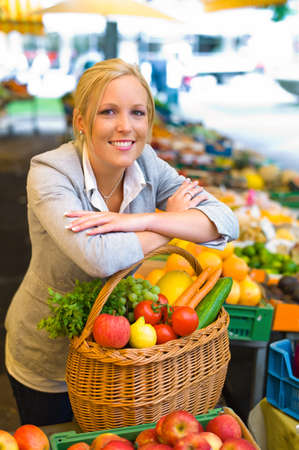 a young woman buying fruits and vegetables at a market  fresh and healthy food  photo