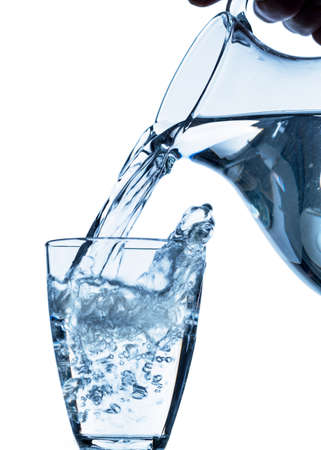 waterworks: pure water is emptied into a glass of water from a pitcher  fresh drinking water