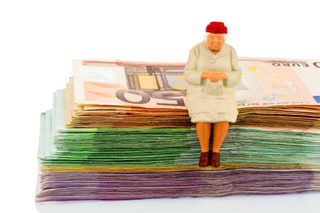 incapacitated: figure of an old woman sitting on a stack of bills, symbolic for pension and retirement Stock Photo