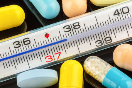 colds: a thermometer and tablets  symbolic for flu and colds
