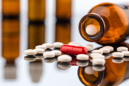 many tablets with a glasbeghäter  symbolic for addiction and costs in medicine and medicines