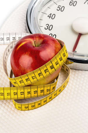 low scale: on a bathroom scale is an apple  symbolic for weight loss and healthy, vitamin-rich diet  Stock Photo