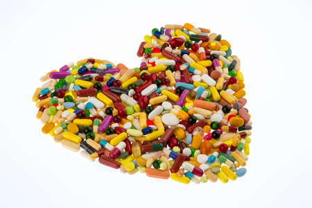 therapie: colorful tablets arranged in heart shape, symbol for heart disease, medication and pharmaceuticals