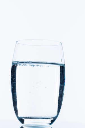 glas met water, symbolisch voor drinkwater, versheid, de vraag en het verbruik
