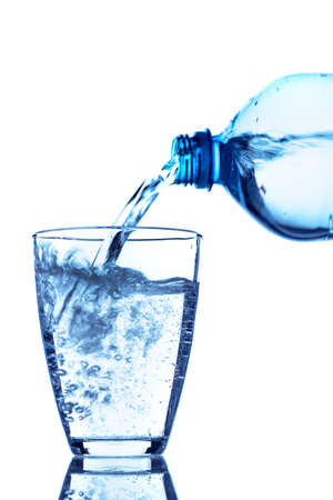 distilled water: from a water bottle of water being poured into a glass Stock Photo